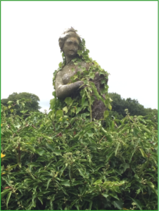 An old statue covered in Ivy